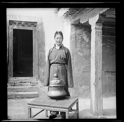 Phunkhang standing behind a bronze vessel on a table