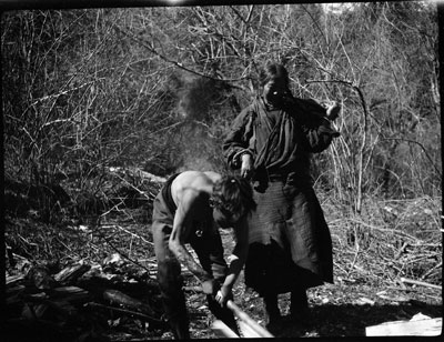Boy chopping wood with his mother